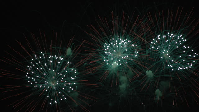 fireworks display with colorful starburst explosives exploding in the night sky, rockets shot up from lower frame bursting, glowing, sparkling and streaking - firework display点の映像素材/bロール