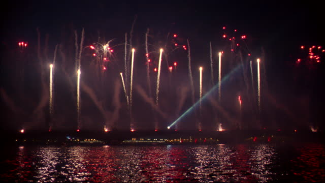 fireworks explode, casting reflections on the water. - sankt petersburg stock-videos und b-roll-filmmaterial