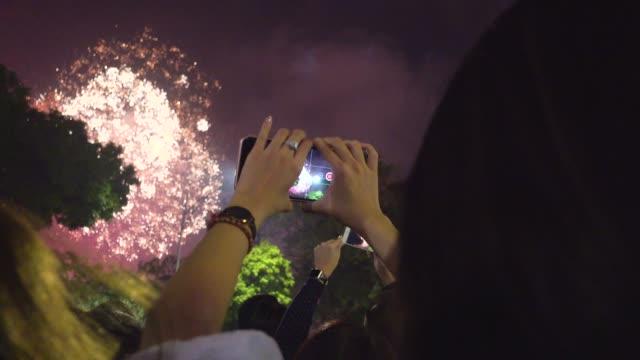 fireworks for tet vietnamese new year celebration. people taking pictures. hanoi hoan kiem old quarter district - 正月点の映像素材/bロール
