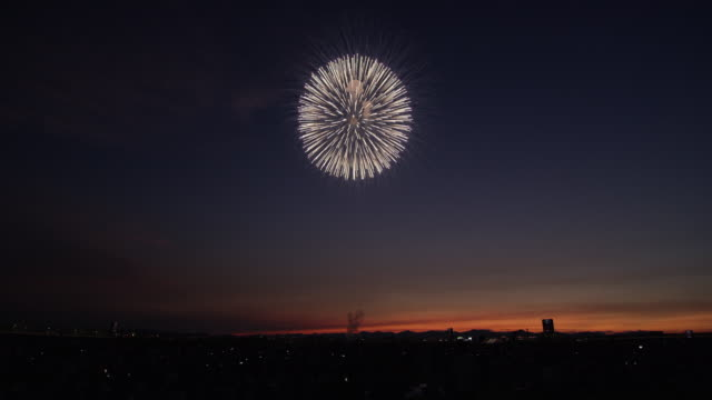 fireworks ignite over nagaoka at sunset, low angle - knallkörper stock-videos und b-roll-filmmaterial
