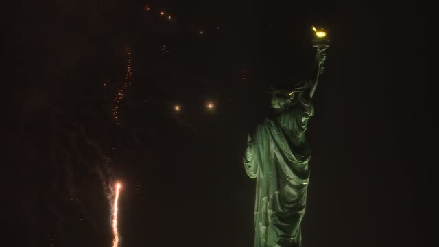 fireworks light up the sky near the statue of liberty during the new year celebrations in new york city, united states on december 31, 2018. - statue of liberty new york city video stock e b–roll