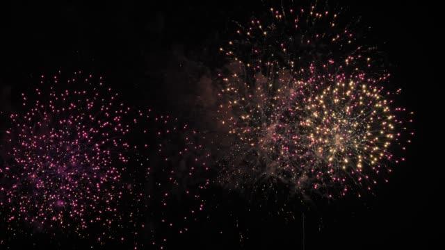 vidéos et rushes de feux d'artifice allument le ciel, feux d'artifice s'affichent sur fond de ciel foncé. célébration du nouvel an. célébration - countdown