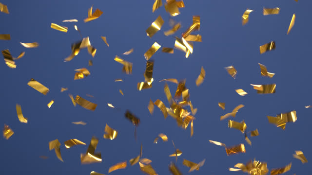 fireworks made of golden confetti on blue background. - tinsel stock videos & royalty-free footage