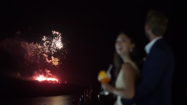 stockvideo's en b-roll-footage met fireworks over island couple blurred - tropische drankjes