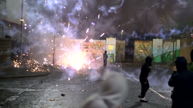 fireworks set off by youths rioting at peace line between shankhill and springfield road, belfast, as tensions rise between loyalists and nationalists - teenager stock videos & royalty-free footage