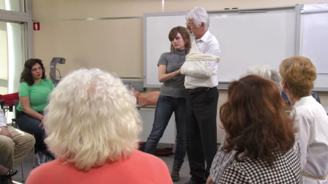 hd: first aid instructor making an arm sling - instructor stock videos & royalty-free footage