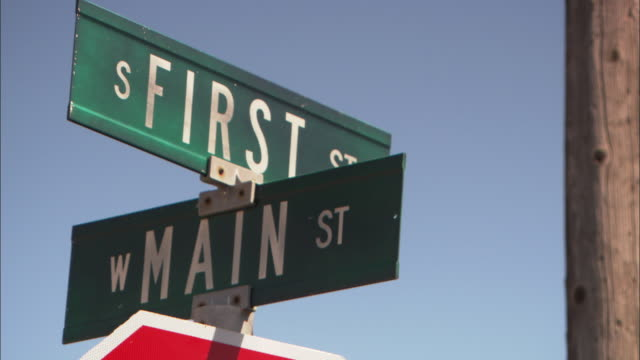 cu td first and main streets and stop signs / wyoming, usa - targa con nome della via video stock e b–roll
