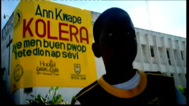 vídeos de stock e filmes b-roll de first anniversary of earthquake; 10 year old boy jean with sign warning of dangers of cholera behind and jean interview sot - hispaniola