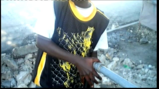 vídeos de stock e filmes b-roll de first anniversary of earthquake; jean showing how children taught to wash hands to protect against cholera using standpipe and other children filming... - hispaniola