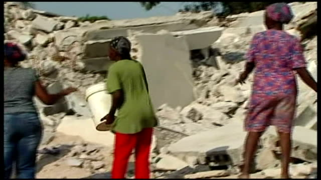 first anniversary of earthquake people passing buckets of rubble along line crosses silhouetted against sky at sunset - haiti stock videos & royalty-free footage