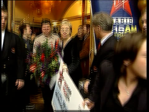 first british quiz show millionaire created; itn ext barwick with bouquet of flowers along evans with barwick and husband simon - gioco televisivo video stock e b–roll