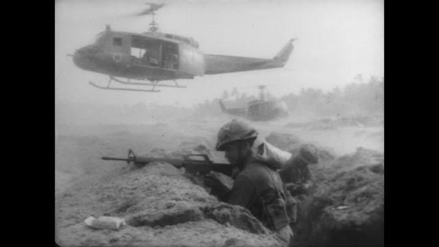 first calvary helicopters landing in vietnam during operation white wing / soldier in trench with helicopter hovering overhead / soldier calls for... - ベトコン点の映像素材/bロール