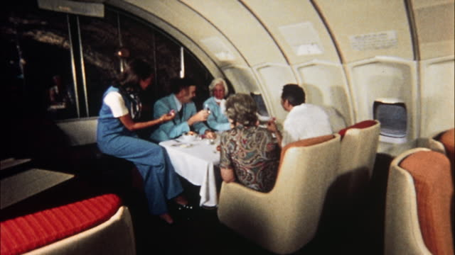vídeos de stock, filmes e b-roll de first class passengers dine at tables while a flight attendant assists other passengers. - interior de transporte