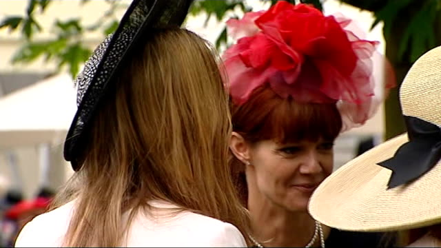 first day of royal ascot; engand: berkshire: ascot: ext women wearing hats and drinking men in top hats drinking champagne women beneath umbrella man... - refreshment video stock e b–roll