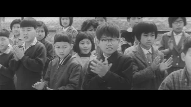first day of school/new enrollments drop at taimei elementary nestled between buildings school starting ceremonies in a giant suburban housing estate... - 小学生点の映像素材/bロール