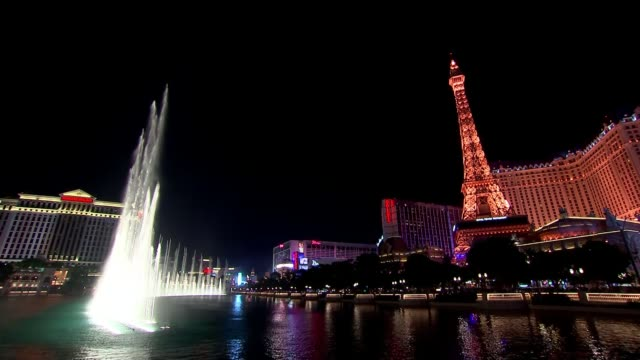 first democratic presidential debate usa nevada las vegas illuminated fountain display with mock eiffel tower hotels and casinos in background close... - las vegas replica eiffel tower stock videos & royalty-free footage