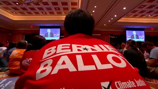 First Democratic Presidential Debate Various of Bernie Sanders supporters cheering him as watching debate on large screens in large room / Vox pop