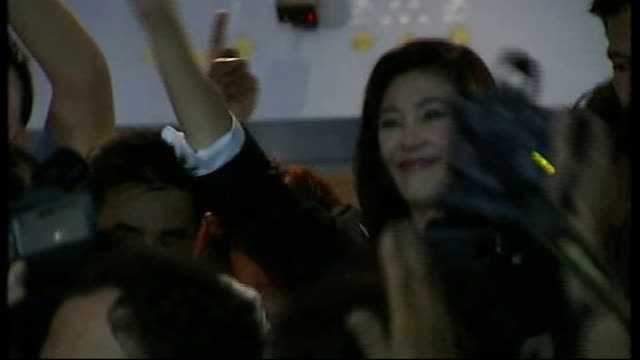 first female prime minister elected; thailand: bangkok: ext reporter to camera cutaway yingluck shinawatra surrounded by photographers taking... - prime minister stock videos & royalty-free footage