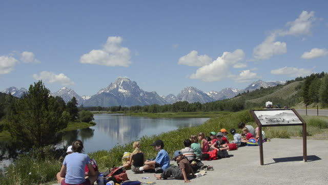 WS First grade students having lunch near reflection of mountain in lake / Jackson Hole, Wyoming, United States