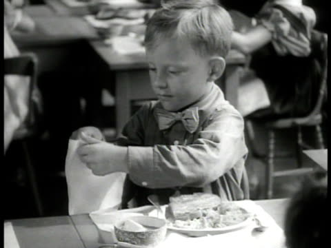 vidéos et rushes de first graders sitting down for lunch. boy tucking napkin under neck. girl eating food. boy sipping from tea cup. two girls talking. cute - règle de savoir vivre