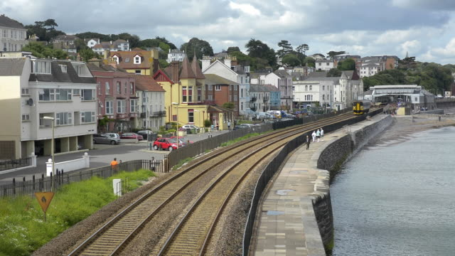 A First Great Western local diesel passenger train traveling along the seawall railway tracks at Dawlish.