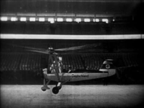 b/w 1937 first helicopter (focke achgelis fa 61) taking off in berlin stadium, germany / industrial - 1937 stock-videos und b-roll-filmmaterial