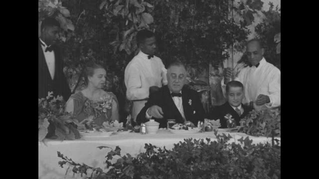 us first lady eleanor roosevelt confers with aide then takes seat at banquet table next to pres franklin roosevelt who chats with a boy seated next... - thanksgiving plate stock videos & royalty-free footage