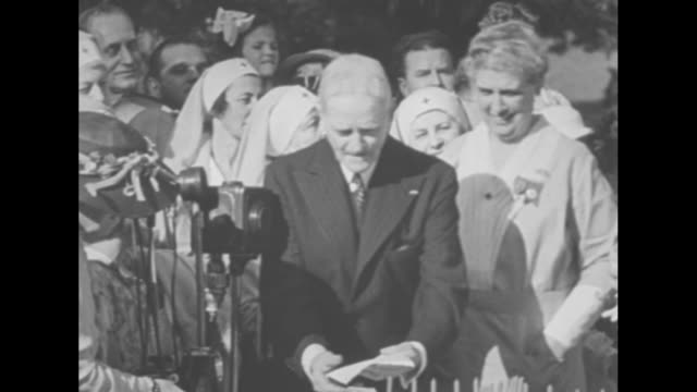 first lady eleanor roosevelt, in a flowered dress, white gloves, and a floppy hat, watches while retired general john pershing cuts cake with a saber... - american red cross stock videos & royalty-free footage