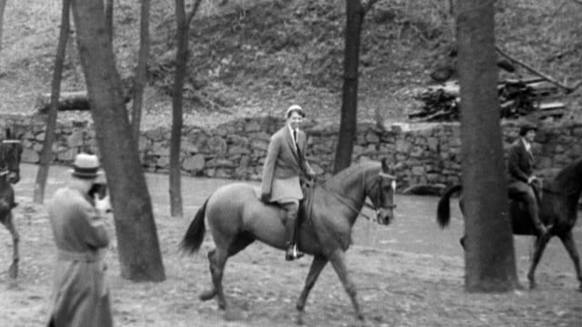 First Lady Eleanor Roosevelt rides down a bridle path accompanied by another woman on horseback and several riders in the rear / Photographers take...