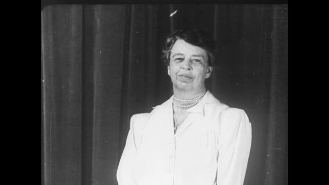 First Lady Eleanor Roosevelt standing on a set in front of large curtains / First Lady sporting an elegant wrap and twirling for the camera / takes...
