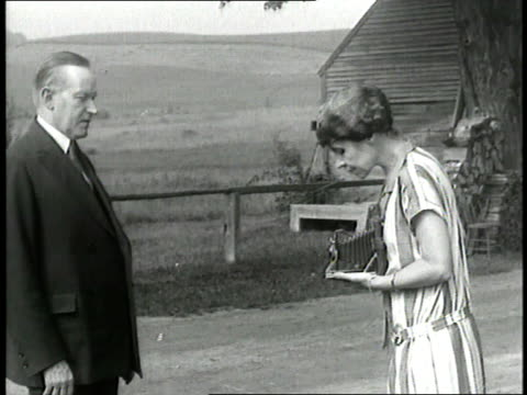 first lady grace coolidge takes a picture of us president calvin coolidge who frowns - 1928年点の映像素材/bロール