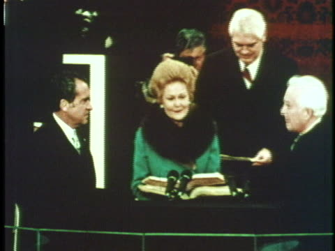 First Lady Pat Nixon holds the bible while her husband Richard M Nixon takes the oath of office from Chief Justice Warren E Burger on January 20 for...