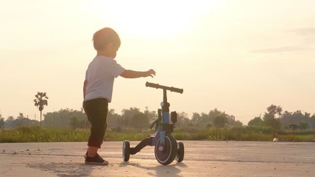 first lessons bicycle riding, happy of asian little boy age 15 months learn to pushing a bike on a tropical vacation while sunset nature.teaching children about sustainability.day in the life of a child concept. - pushing stock videos & royalty-free footage