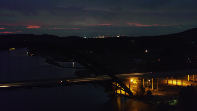 first light behind pennybacker bridge in austin, texas - aerial - südwestliche bundesstaaten der usa stock-videos und b-roll-filmmaterial
