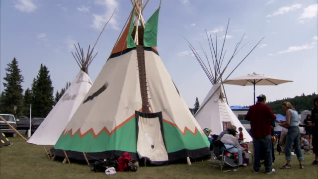 A First Nations couple Tribe sits outside their teepee at a Pow Wow. Available in HD.