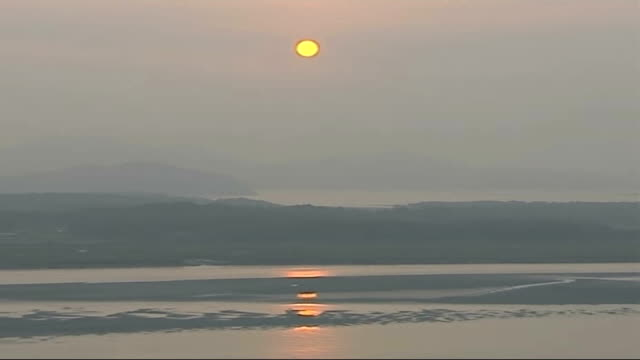first nuclear test further world reaction border with north korea long shots of watery sunset over north korea and demilitarised zone - kernwaffentest stock-videos und b-roll-filmmaterial