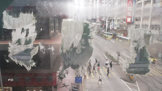 first person charged under new security laws hong general views of school children along close shots of window with posters torn down - politics stock-videos und b-roll-filmmaterial