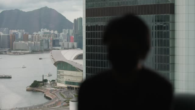 first person charged under new security laws hong kong int anonymous interview with man looking to leave hong kong for uk - politics stock-videos und b-roll-filmmaterial
