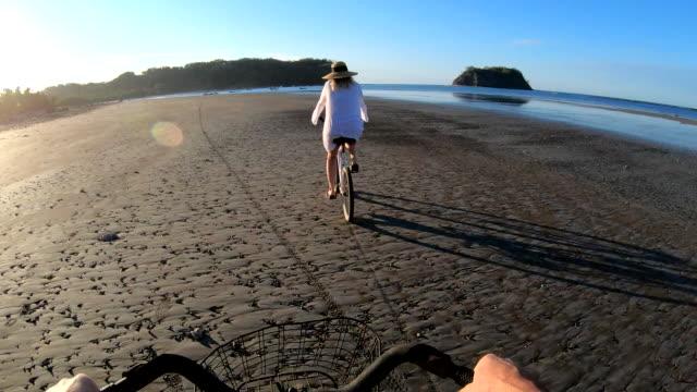 första person perspektiv som kvinna cyklar längs tidvattenlägenhet vid soluppgången - korg bildbanksvideor och videomaterial från bakom kulisserna