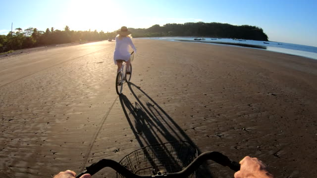 first person perspective as woman bicycles along tidal flat at sunrise - costa rica stock videos & royalty-free footage