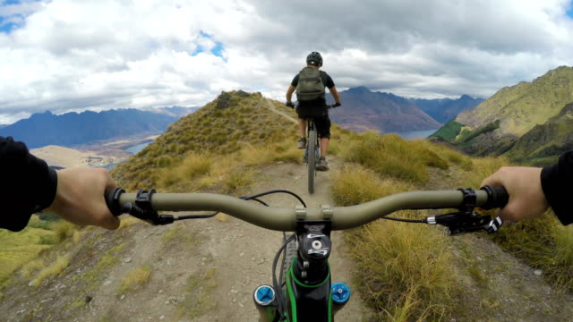 first person perspective following a mountain biker down picturesque ridge line - andare in mountain bike video stock e b–roll
