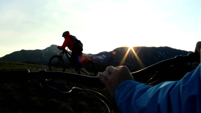 first person perspective following another mountain biker as he pushes up alpine slope at sunrise. - jacket stock videos & royalty-free footage