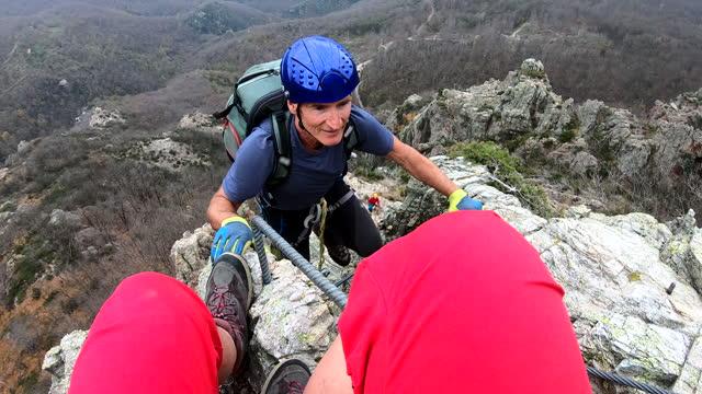 vidéos et rushes de perspective à la première personne de l'ascension «via ferrata» le jour nuageux - 55 59 ans