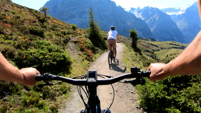 first person perspective of e-biking along mountain path - convenience stock videos & royalty-free footage