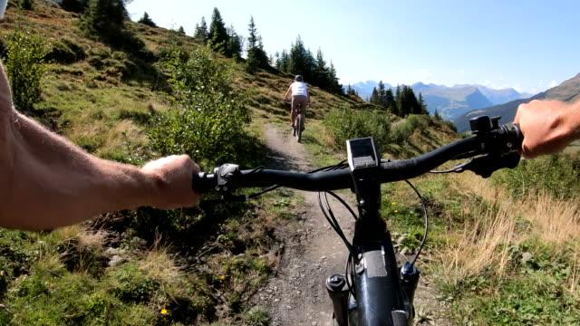 vídeos de stock e filmes b-roll de first person perspective of e-biking along mountain path - guiador