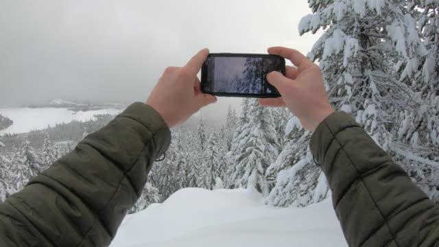 vídeos y material grabado en eventos de stock de perspectiva en primera persona (pov) de las manos del excursionista tomando una foto panorámica con teléfono inteligente - nevosa