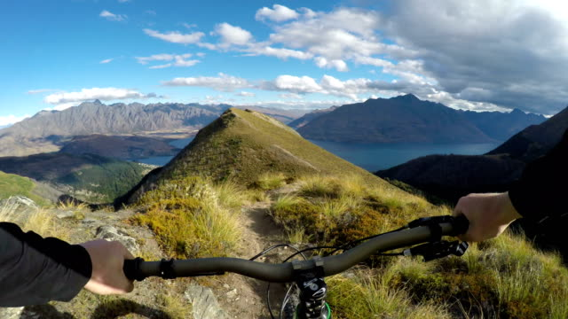 First person perspective of mountain biker descending hilly ridge line above iconic lake