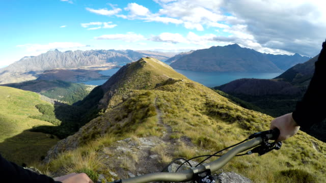first person perspective of mountain biker descending hilly ridge line above iconic lake - ridge stock videos & royalty-free footage