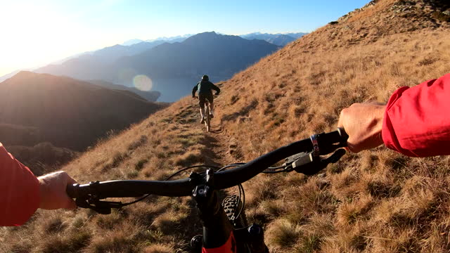 first person perspective of mountain biking along top of a mountain at sunrise - mountain biking stock videos & royalty-free footage