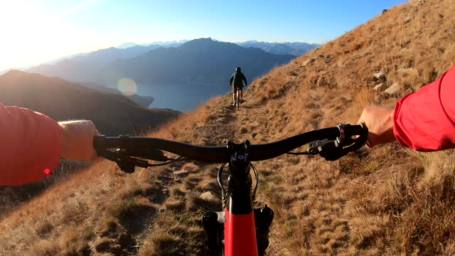 stockvideo's en b-roll-footage met first person perspective of mountain biking along top of a mountain at sunrise - herinneringen